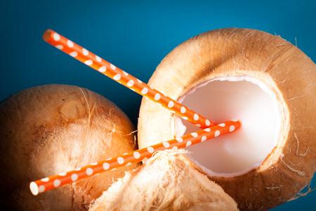 Coconuts with open one of them and orange straws to drink fresh water Zdjęcie Seryjne
