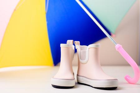 zapatos de seguridad: Las botas de goma rosadas de los niños pequeños se colocan bajo el paraguas colorido, concepto del fondo del otoño o de la primavera. Foto de archivo