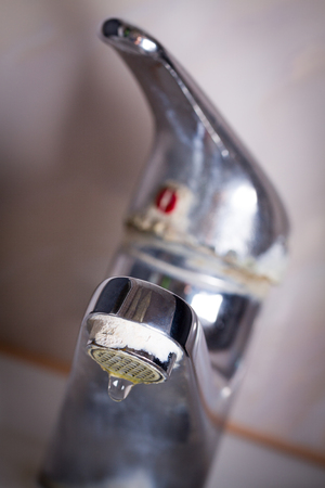 Old leaking faucet with stone and calcium sediments due to hard water.