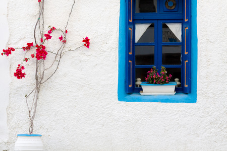 Traditional greek wall with blue window and red flowers.