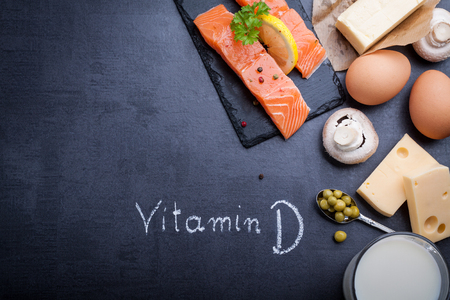 Black slate table with product rich in vitamin D and omega 3. Written word vitamin D by white chalk. Stock Photo