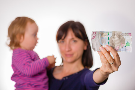 Mother with little daughter holds in hand 500 zloty banknote. Symbol of 500 + polish program for families.