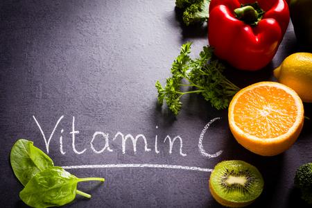 Frutas y verduras ricas en vitamina C con inscripción de palabra blanca por tiza y copia espacio en pizarra negra. Foto de archivo
