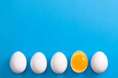 White eggs is laying in row, one of them is bisected and shows yolk.  Stock Photo