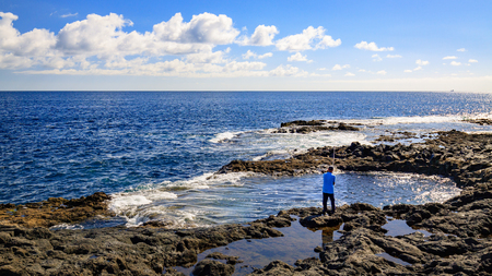 Angler on El Bufadero, rocky seashore on Gran Canaria island, Spain. Stock Photo