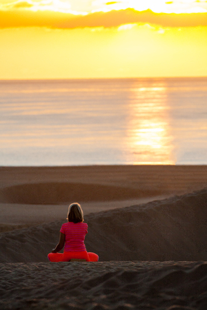 Woman doing yoga (sit) on sand dunes in Maspalomas. Stock Photo