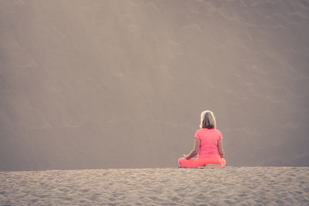 Woman doing yoga (sit) on sand dunes in Maspalomas. Stock Photo