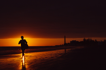 Walker on seashore with lighthouse during sunset in Maspalomas, Gran Canaria Island. Stock Photo