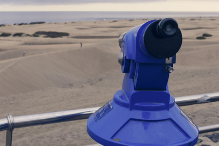 Coin-operated binocular looking out sand desert dunas and coastline.