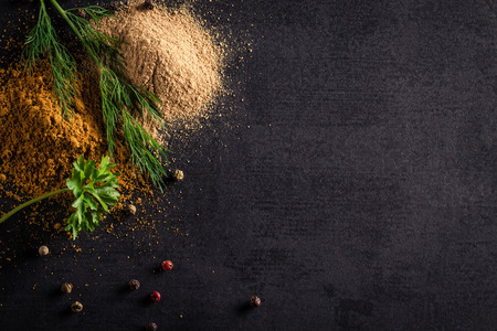 Background of two heaps of spice and pepper, parsley and fennel.