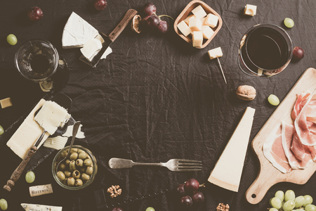Palette of many types of cheese and some grapes, olives and wine with copy space. Фото со стока