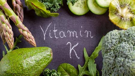 Green vegetables rich in vitamin K on black slate.