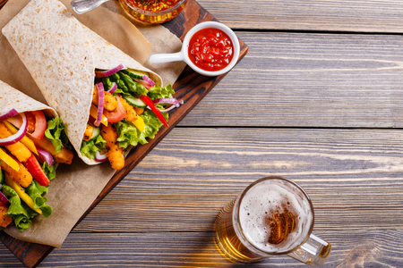 Tortilla with chicken and vegetables and beer to drink.