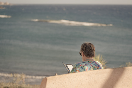 Older woman is sitting on bench with view on sea and she is reading ebook on her reader.