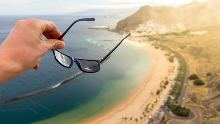 Hand keeps the sunglasses with Teresitas beach on fuzzy background. Stock Photo