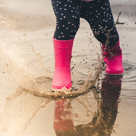 Feet of child in pink rubber boots jumping and splashing over puddle after rain. Stock Photo