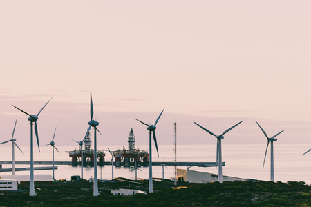 Group of windmills and solar panels for electric power production and oil rigs on coast. 版權商用圖片