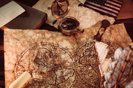 Old vintage maps and marine equipment like compass, magnifier or hourglass and ship. Columbus Day concept. Editorial