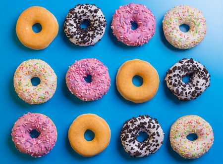 Top view of many colorful donuts on blue