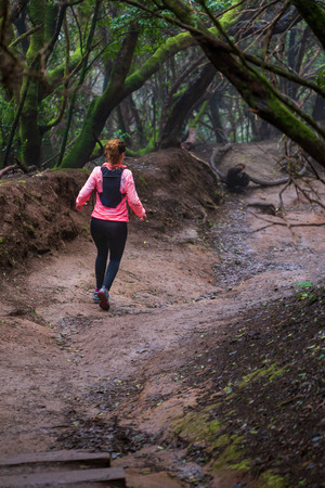 Young woman running in rain forest on Tenerife Island. Archivio Fotografico
