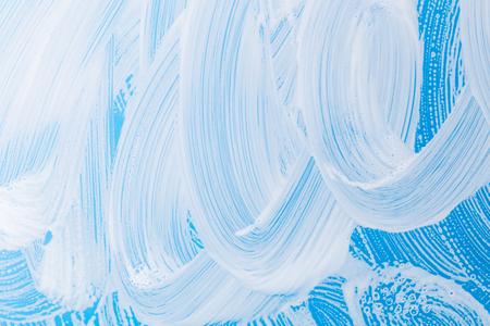 Foam of detergent on blue glass