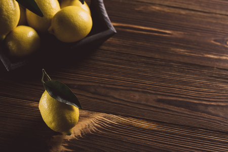 Fresh yellow lemons with leaves on wooden table.