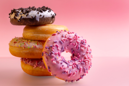 Stack of colorful donuts on pink background.