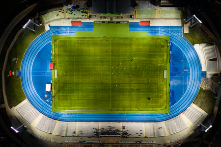Football stadium at night light, top down view on soccer players.