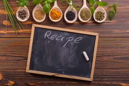 Mixed spices and herbs on wooden spoons with blackboard. Stock Photo