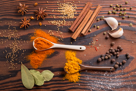 Mixed spices and herbs in kitchen utensils on wooden background.