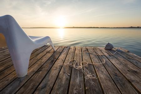 Landscape with empty chair in wooden footbridge on Powidzkie Lake in Poland.