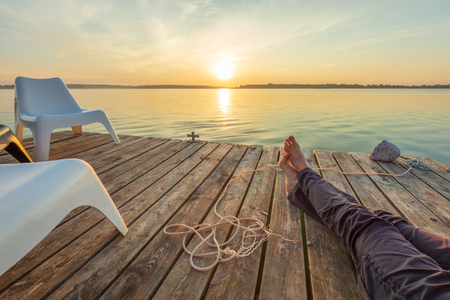 Man relaxing on footbridge with naked foot. Concept of waiting for summer. Stock Photo