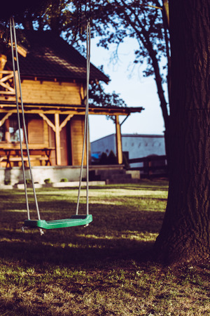 Empty swing in forests garden with wooden house.