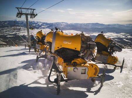 Yellow snow cannons on slope in winter time.