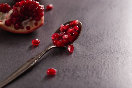 Fresh pomegranate fruits with red seeds on spoon in dark scenery. 版權商用圖片