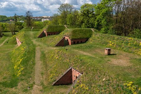 Bunkers covered with ground and grass, dugouts made by bricks and steel hidden under hill. Фото со стока