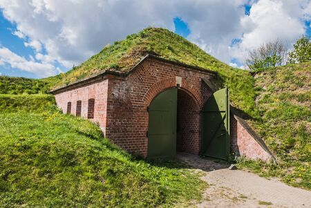 Bunker covered with ground and grass, dugout made by bricks and steel hidden under hill.