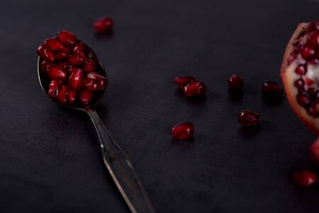 Fresh pomegranate fruits with red seeds on spoon in dark scenery.