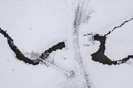 Aerial view on small stream and fallen tree in snowy winter.