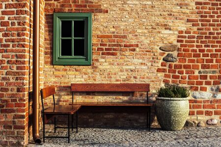Empty bench in brick wall corner with small window. Vintage styles photography. Place inviting on rest. 版權商用圖片