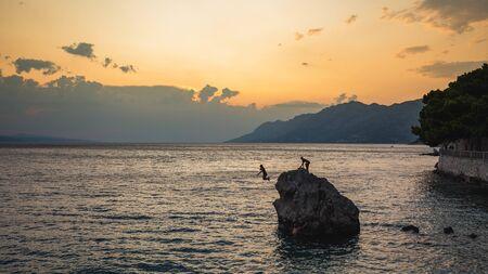 若者は大きな石、ブレラ、クロアチアから水にジャンプしています。