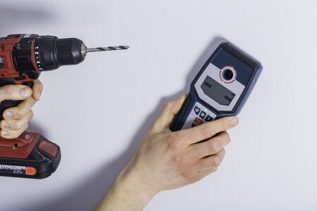 Man hand is scanning wall by cable detector to find a cable before drilling in.