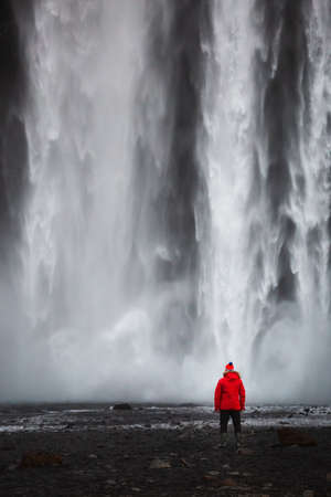 Red clothed man standing in front of water wall of the famous Icelandic waterfall called Seljalandsfoss. View to your calendar or postcard.