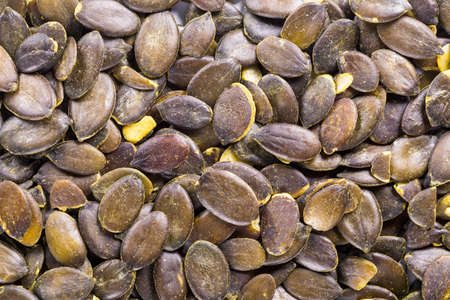 Background of big raw pampkin seeds, situated arbitrarily. 免版税图像