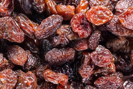 Background of big raw dried raisins, situated arbitrarily. 免版税图像