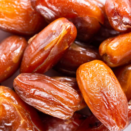 Background of big raw dried dates, situated arbitrarily. 免版税图像