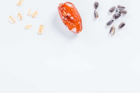 Sunflower seeds, oats and dried dactyl on white background with copy space. 免版税图像