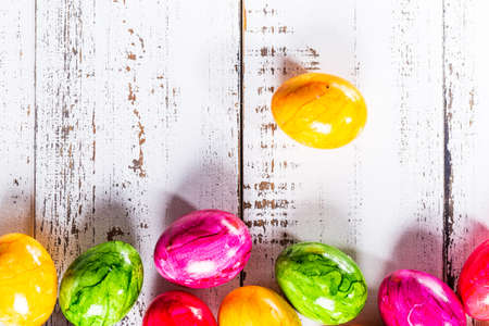 Easter wooden background with colored eggs.