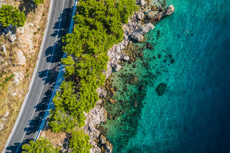 Top view of rocky coastline with turquoise water.