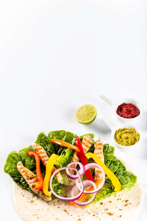 Ingredients for preparing tortilla with fresh vegetables, chicken and sauce. Flat lay view on white background.